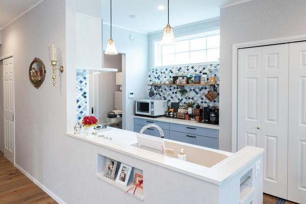 落ち着いた配色のカラータイルと、ペールブルーのキッチン
